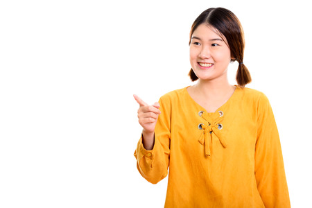 Studio shot of young happy Asian woman smiling while pointing fi