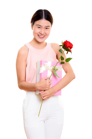 Young happy Asian woman smiling while holding red rose and gift