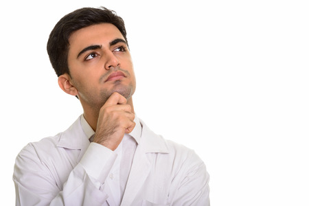 Young handsome Persian man doctor thinking and looking up