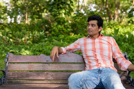 Indian man thinking while sitting on wooden bench in peaceful gr