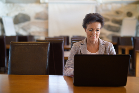 Mature Beautiful Businesswoman Using Laptop At The Coffee Shop