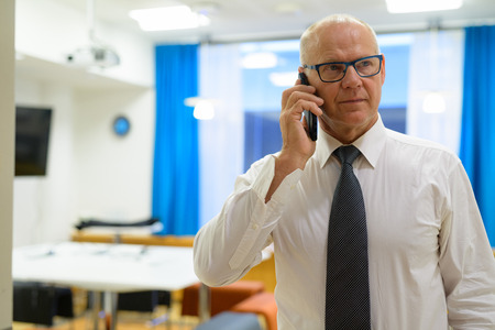 Senior Businessman Thinking While Talking On Phone In The Office