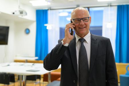Happy Senior Businessman Talking On The Phone At Work