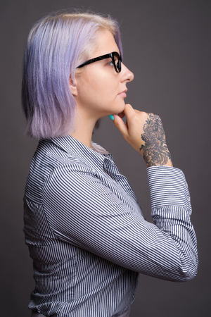 Profile view of businesswoman with short colorful hair thinking