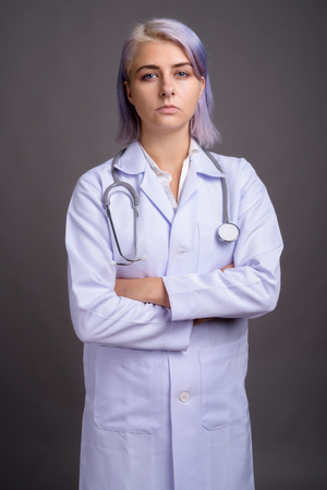 Young beautiful woman doctor with short colorful hair against gr