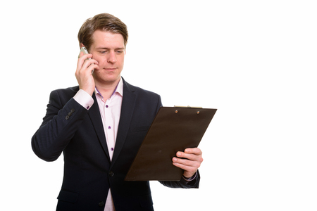 Handsome Caucasian businessman reading clipboard while talking o Imagens
