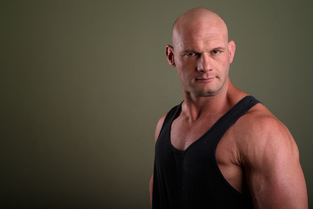 Bald muscular man wearing tank top against colored background