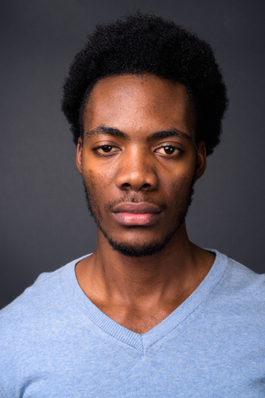 Face of young handsome African man against gray background Stock Photo