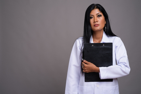 Mature beautiful Asian woman doctor against gray background