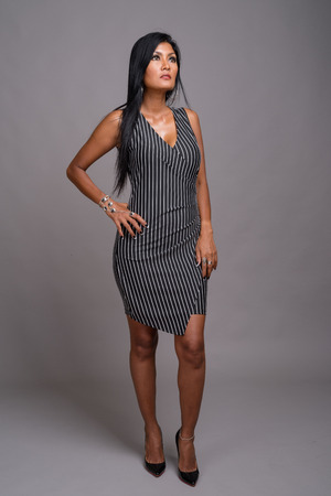 Mature beautiful Asian woman against gray background 免版税图像