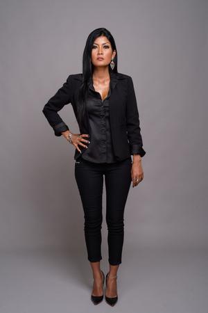 Mature beautiful Asian businesswoman against gray background