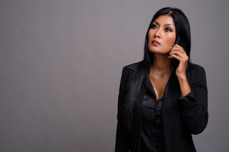 Mature beautiful Asian businesswoman against gray background
