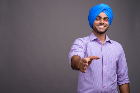 Young handsome Indian businessman wearing turban against gray ba