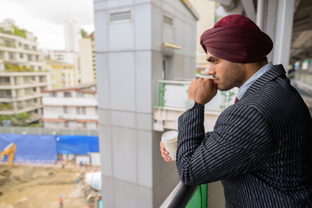 Indian businessman looking at construction development site with skyscrapers