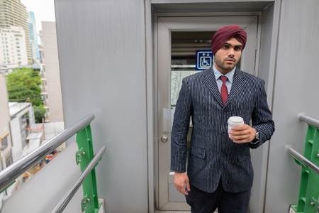 Portrait of Indian businessman with turban outdoors in city holding coffee cup