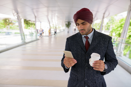Indian businessman in city using phone and holding coffee cup