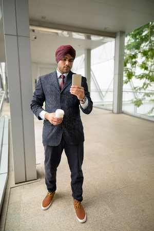 Indian businessman in city holding coffee cup and mobile phone