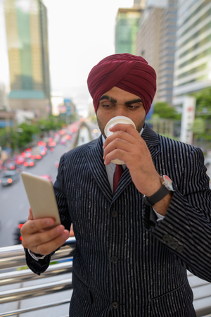 Indian businessman outdoors in city using mobile phone and drinking coffee