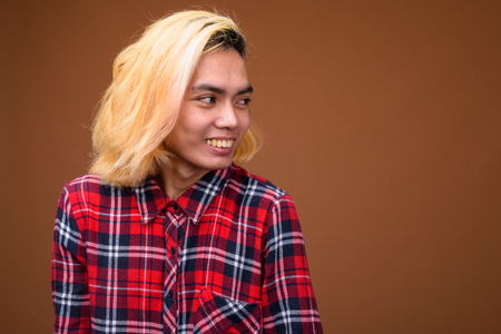 Young Asian man wearing stylish clothes against brown background