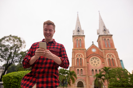 Tourist man using phone in front of Notre Dame Cathedral in Ho Chi Minh City
