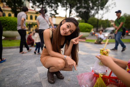 Young beautiful Asian tourist woman ordering food and making cute pose