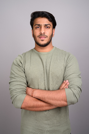 Portrait of young handsome Indian man against gray background