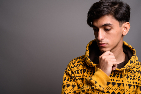 Sad Persian teenage boy thinking against gray background