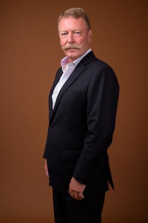 Bel homme d'affaires senior avec moustache portant un costume
