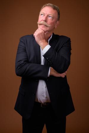 Un bell'uomo d'affari anziano che pensa e guarda in alto