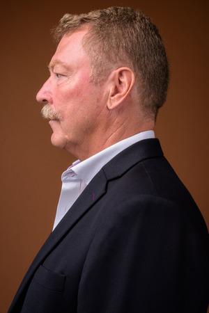 Vista di profilo dell'uomo d'affari senior con i baffi che indossano la tuta Archivio Fotografico
