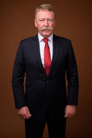 Uomo d'affari anziano bello che indossa giacca e cravatta