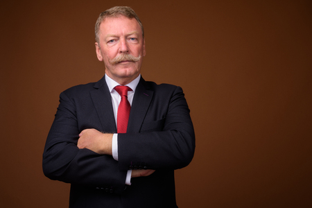 Bello uomo d'affari anziano che indossa giacca e cravatta con le braccia incrociate