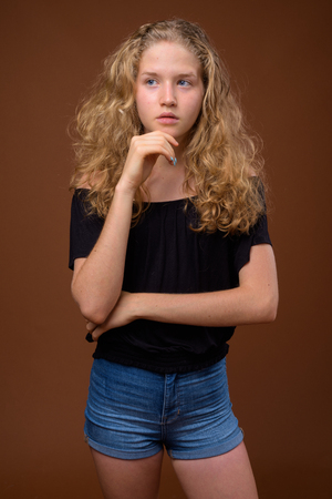 Young beautiful blonde teenage girl thinking against brown background