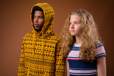 Portrait of young African man and Caucasian teenage girl thinking Stock Photo