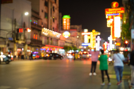 Blurred view of people crossing in the streets of Chinatown in Bangkok at night