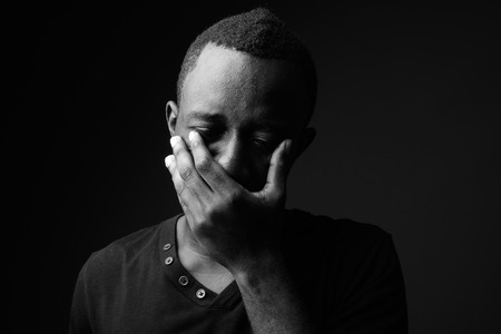 Sad young African man against black background in black and white