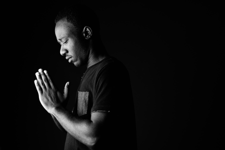 Sad young African man praying in black and white 写真素材