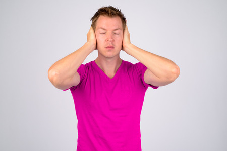 Young handsome man covering ears as hear no evil concept Stock Photo