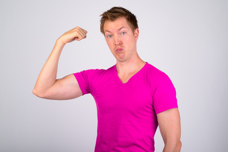 Funny young man making face while flexing muscles Stock fotó