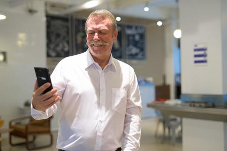 Happy senior businessman using phone at the coffee shop Standard-Bild