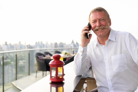 Happy senior businessman smiling while calling with phone at the rooftop restaurant 免版税图像 - 113725635
