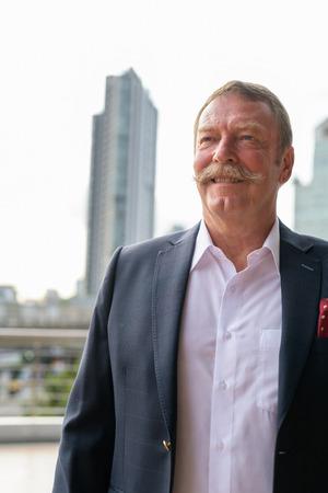 Heureux homme d'affaires senior souriant et pensant contre la vue sur la ville Banque d'images