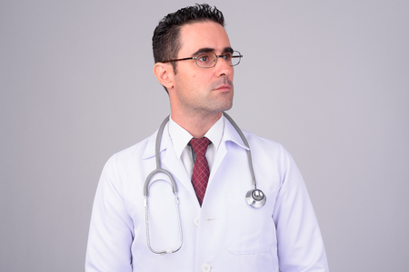 Portrait of handsome man doctor against white