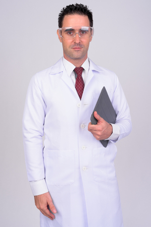 Handsome man doctor with protective glasses holding digital tablet