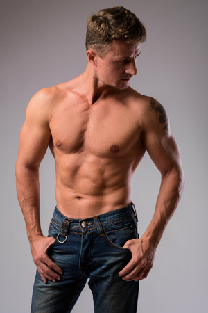 Muscular handsome bearded man shirtless against white background