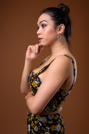 Profile view of young beautiful Asian transgender woman thinking