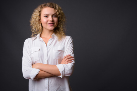 Young beautiful businesswoman with curly blond hair against gray