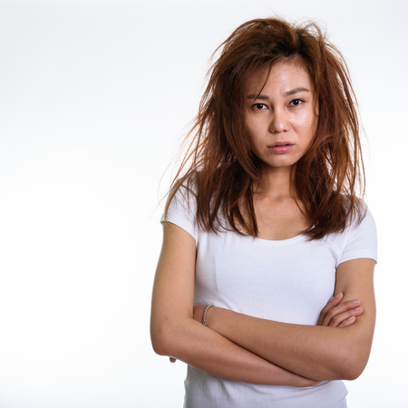 Studio shot of young Asian woman with arms crossed and messy hair