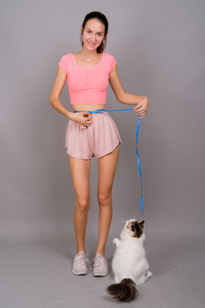 Young beautiful woman ready for gym measuring waist with cat Фото со стока