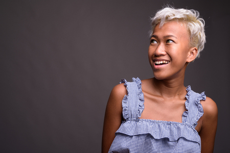 Young beautiful woman with short hair smiling and thinking